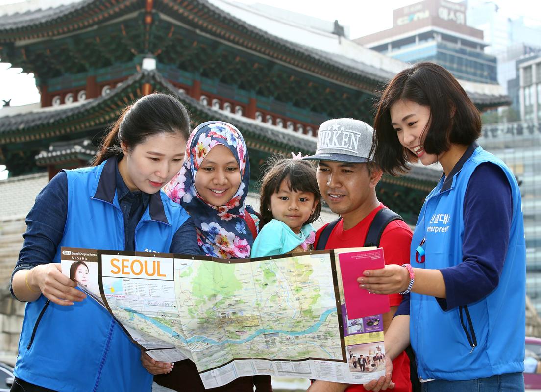(재)한국방문위원회의 통역자원봉사단 '친절대사'들이 28일 서울 숭례문을 찾은 외국인 관광객들에게 지도를 보며 안내를 하는 모습.